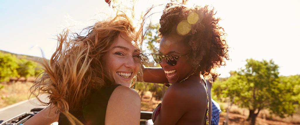 Twee vrouwen in de auto met zonnebril