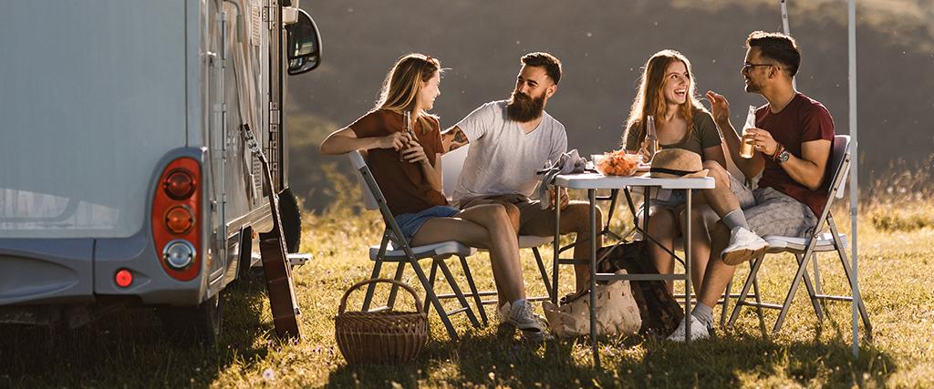 Kamperen met camper en groepje vrienden bij zonsondergang